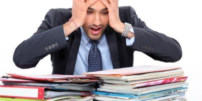 Frustrated business person looking over a pile of papers that would benefit from scanning