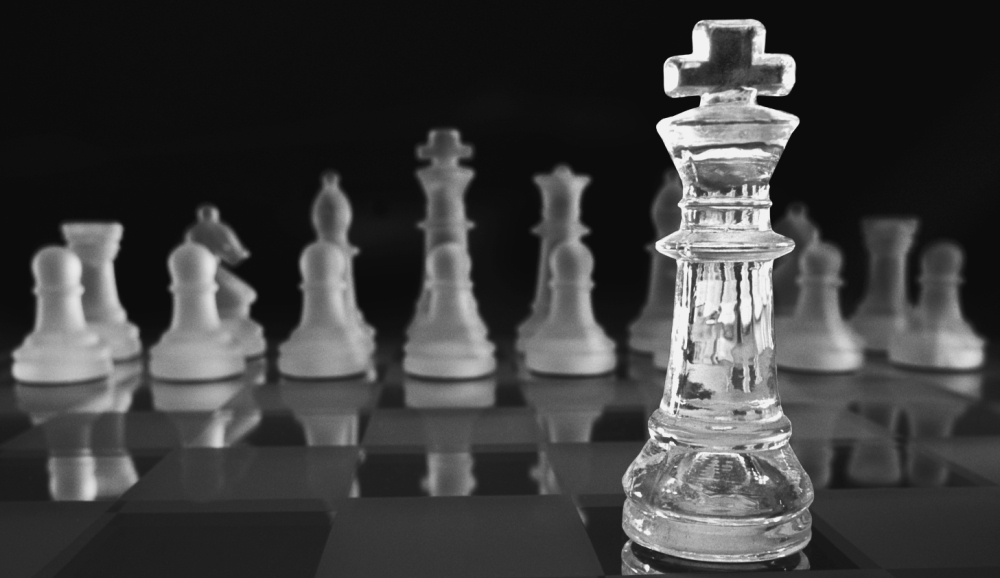 A chess board with the King piece out in front of the rest of the pieces